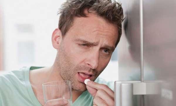 Мужчина принимает таблетку