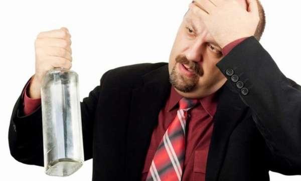 Мужчина держит в руке бутылку водки