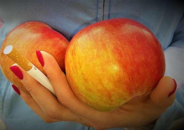 Яблоки и сигарета в руке