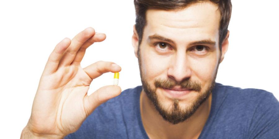 Парень держит таблетку