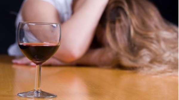 Девушка сидит рядом с бокалом вина