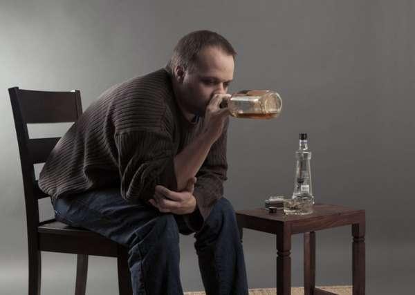 Мужчина пьет спиртное из бутылки