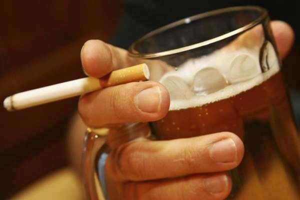 Алкоголь и сигарета в руке