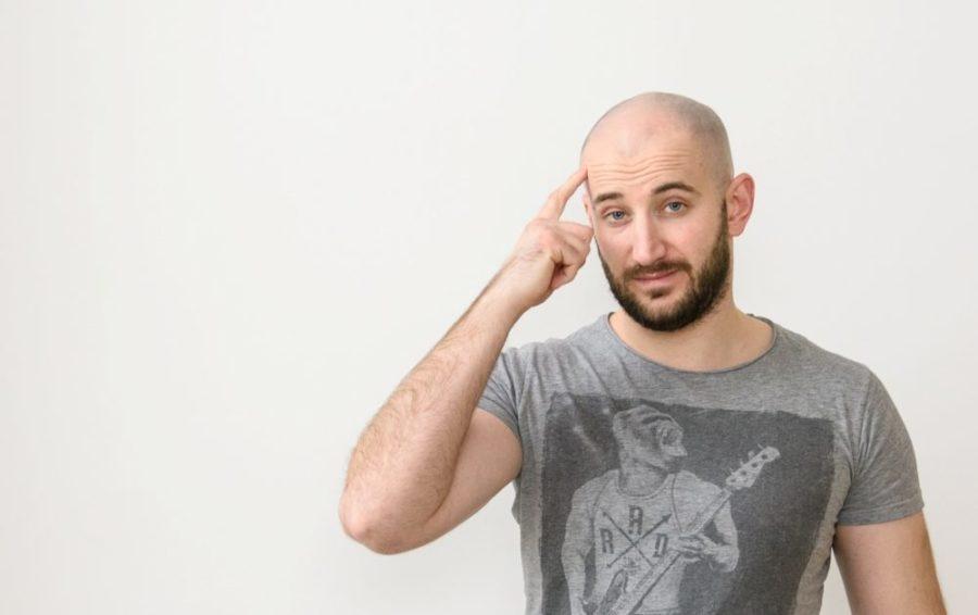 Мужчина держит палец у головы