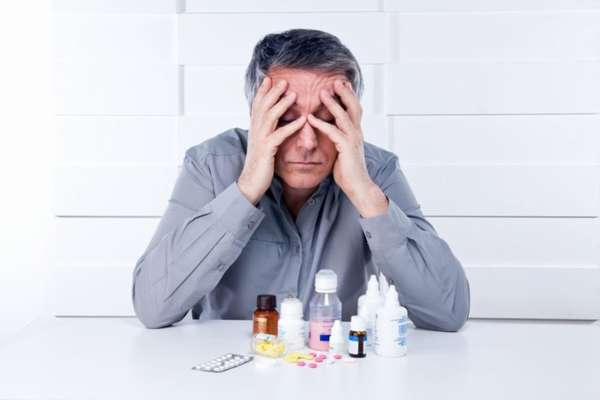 Мужчина сидит над таблетками