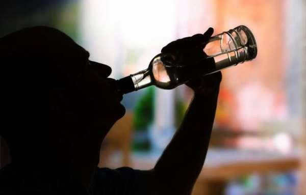 Мужчина пьет из бутылки