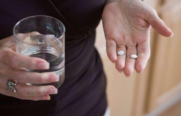 Таблетки с стакан воды в руках