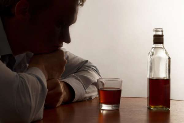 Мужчина смотрит на стакан со спиртным