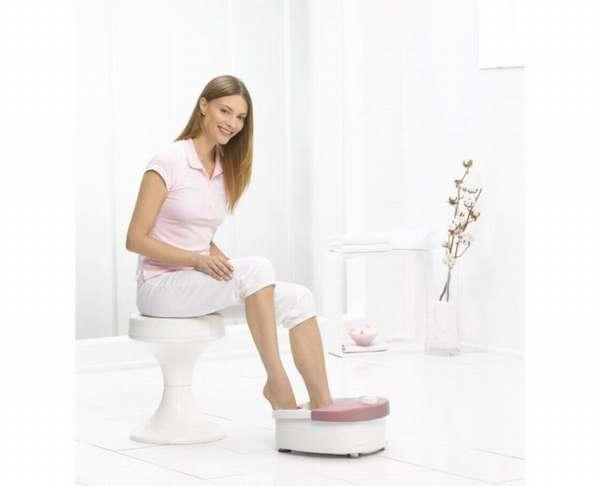 Женщина принимает ванночку для ног
