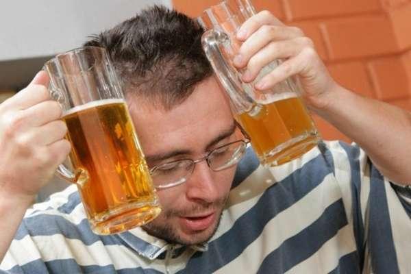 Мужчина держит бокалы с пивом у головы