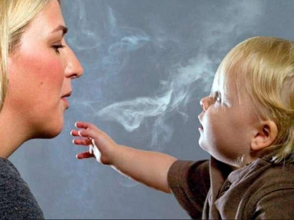 Мать выдыхает дым на ребенка