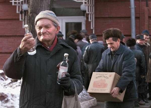 Мужчина рассматривает бутылку водки