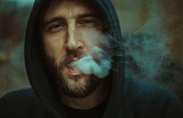 Мужчина выпускает дым