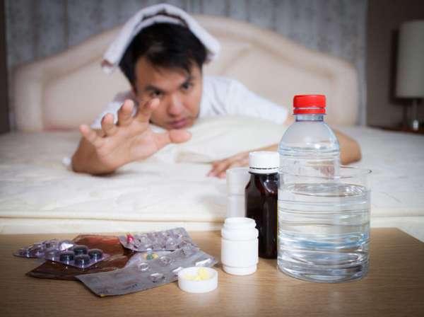 Мужчина тянется к лекарствам