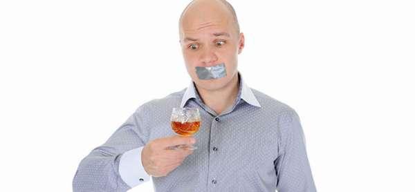 Мужчина со скотчем на рту смотрит на рюмку