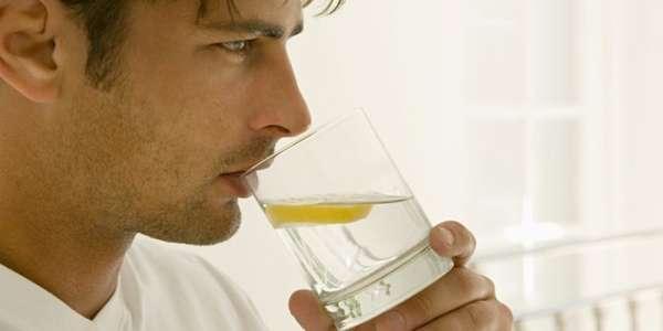 Парень пьет воду с лимоном