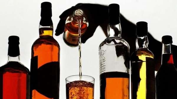 Человек наливает алкоголь в стакан