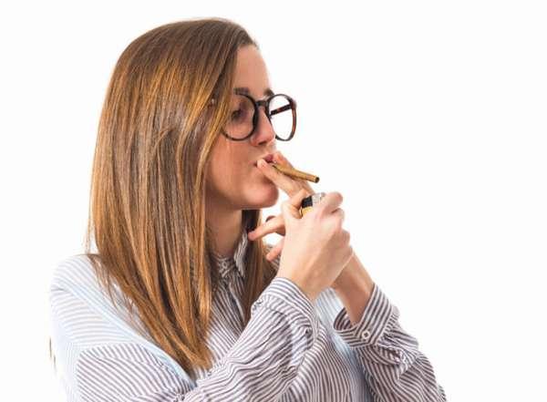 Девушка подкуривает сигарету
