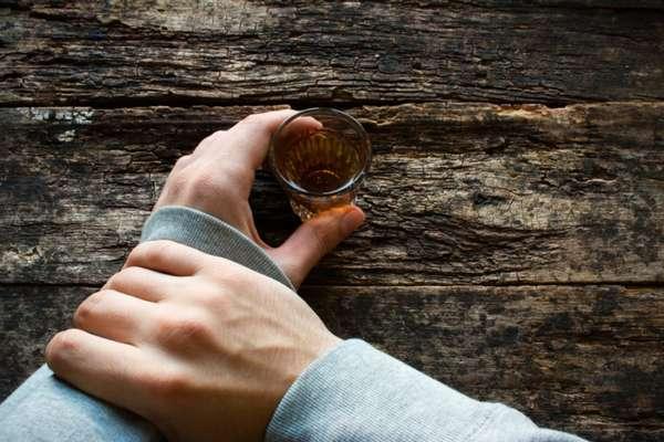 Рюмка с алкоголем в руке