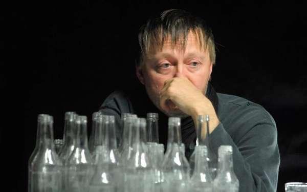 Мужчина сидит рядом с бутылками