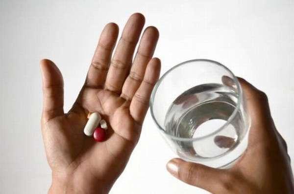 Человек держит таблетки и бокал